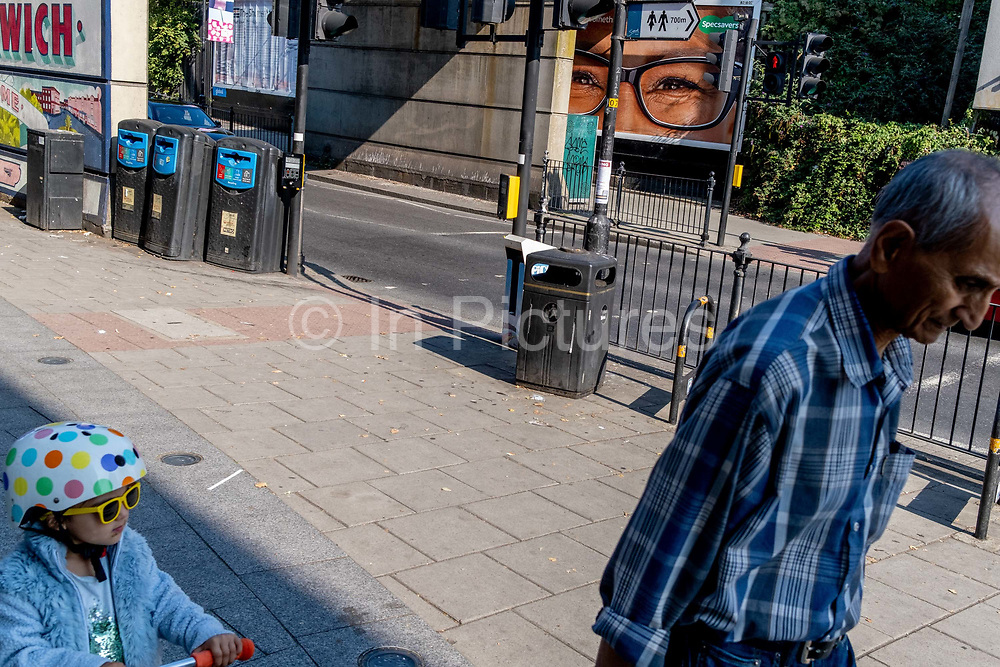 A pair of eyes and glasses frames from an ad for opticians retailer Specsavers, and a young girl wearing her own sunglasses, on 14th Septermber 2020, in East Dulwich, London, England.
