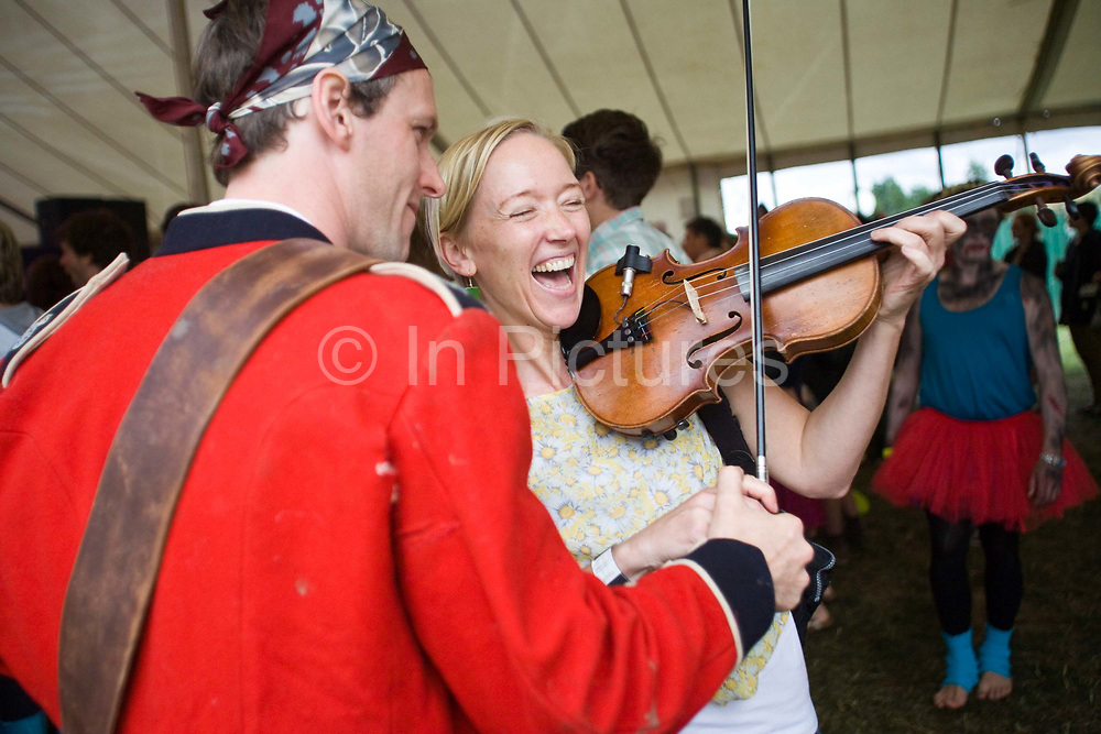 A woman laughs as she plays a violin at the Standon Calling Festival in Hertfordshire, UK..Standon Calling is a small independent festival set among the hills in Herfordshire that showcases World Music, Indie Music and dance Music. It is one of the new, small and quirky boutique festivals which have become popular in the UK...