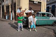 CUBA: Havana. children's fashion for boys in a street of Havana centro area. with cubanos musicians      / Cuba. La Havane.  mode enfantine pour garcon. dans une  rue de  La Havane Centro, avec des musiciens cubains    ,