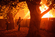 Firefighters battle the Glass Fire as it burns into backyards in the Stonegate neighborhood of Santa Rosa, California on the night of September 27-28, 2020