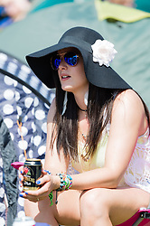 © Licensed to London News Pictures. 11/06/2015. Newport, UK.  A female festival goer wearing a big floppy hat to shield her face from the hot sun at Isle of Wight Festival 2015 drinks beer out of a beer can hat on day 1 of the festival.  Today has been hot and sunny.  This years festival include headline artists the Prodigy, Blur and Fleetwood Mac.  Photo credit : Richard Isaac/LNP