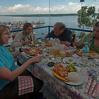 Geo-tourists enjoy lunch in a restaurant overlooking the busy Amazon River harbor in Iquitos, Peru.