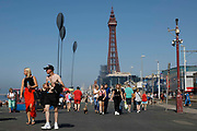 Domestic tourists and dog walkers walk up the promenade with the world famous Blackpool Tower in the background as temperatures in the country are expected to soar this week on 7th September, 2021 in Blackpool, United Kingdom. Temperatures in the UK are predicted to soar to highs of 29 degrees celsius, coinciding with a rise in daycation and staycation domestic tourism in the country as a result of Covid-19 precautions that make foreign travel increasingly costly and difficult.
