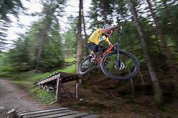 Mountain biker jumping with speed on forest path, Trentino-Alto Adige, Italy