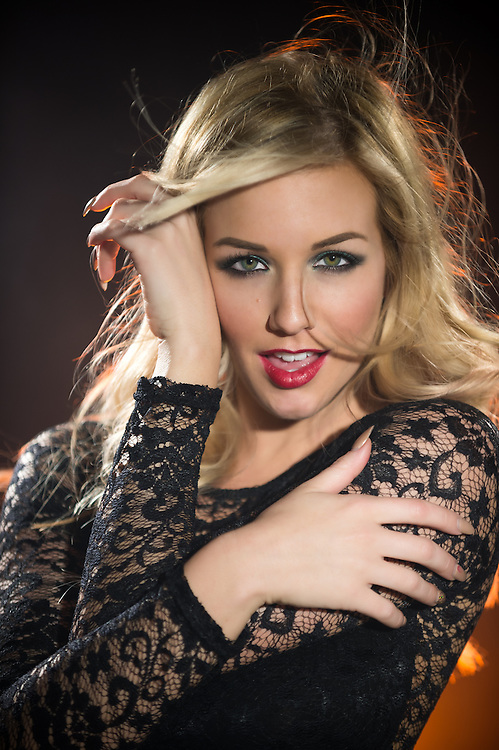 Portrait of sensual blonde woman smiling and looking at camera happy and with hair flying.