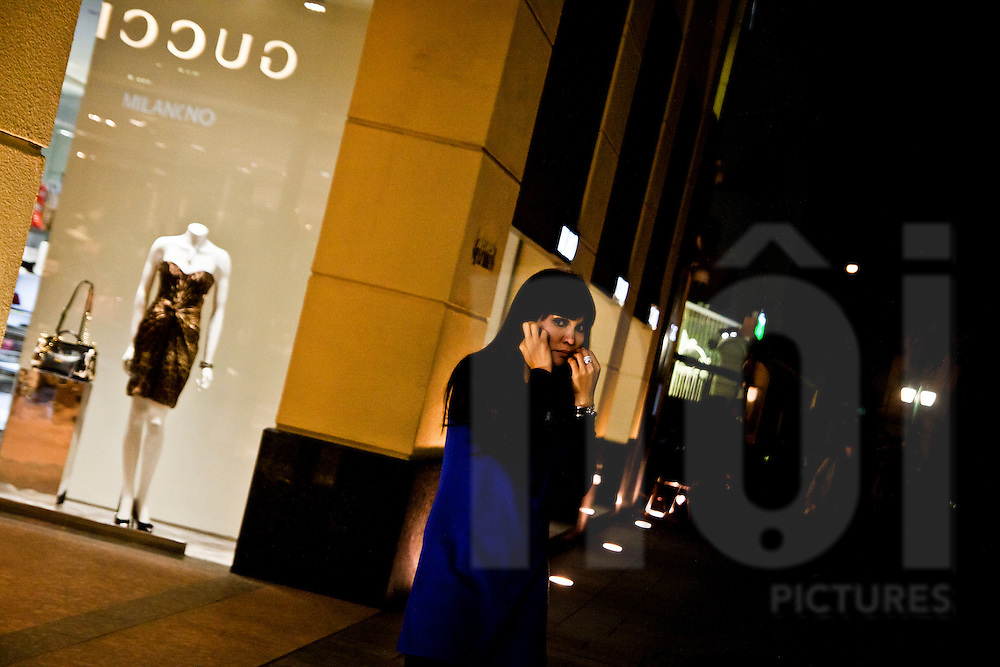 A woman makes a phonecall outside a Gucci shop in the centre of Hanoi, Vietnam