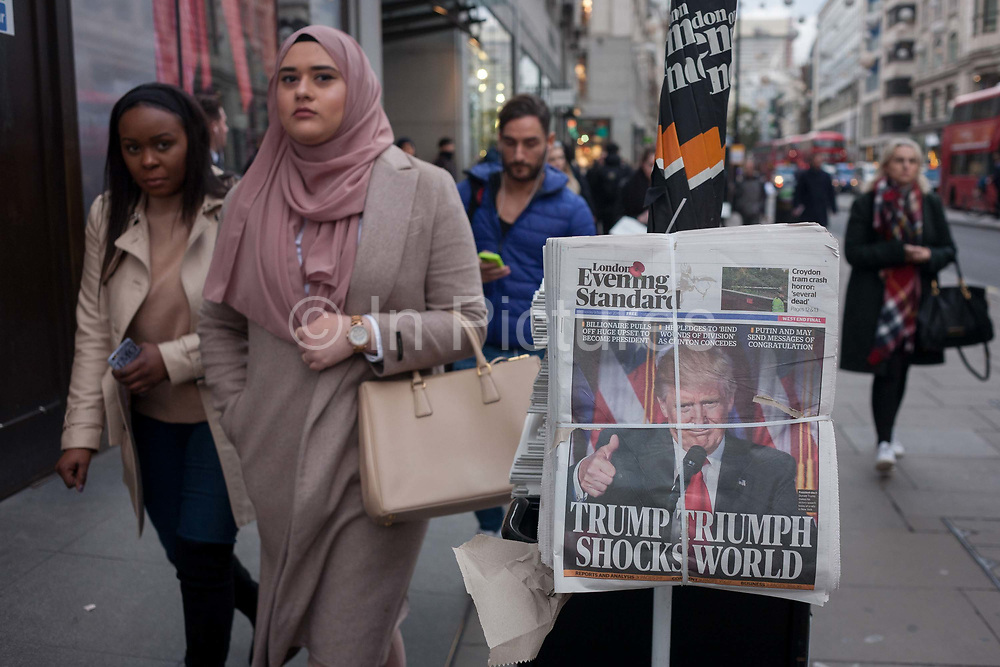US president-elect, Donald Trump appears on the front page of the London Evening Standard newspaper, on the day of his election, on November 9th 2016, in central London, England. The headline reads Trump Triumph Shocks World and Londoners of all colours and races take the free paper to read the latest overnight news.