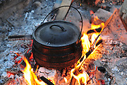 Cooking on an open fire, an iron caldron on an outdoor wood fire, hand stirring the broth