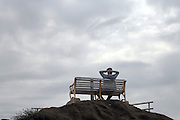 single person sitting on bench on top of a hill