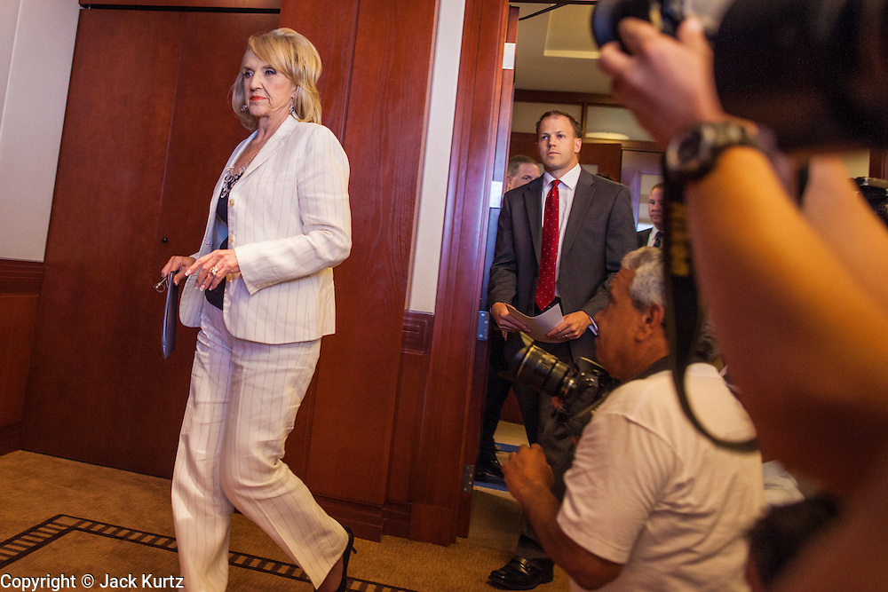 25 JUNE 2012 - PHOENIX, AZ:  Arizona Governor JAN BREWER walks into a press conference in her office to respond to the US Supreme Court ruling that overturned most of SB 1070, the state's tough anti-immigration bill, duing a press conference Monday. Brewer said the state won a major victory in the court's ruling because a narrow portion of the law was allowed to stand. The lawsuit, US v. Arizona, determines whether or not Arizona's tough anti-immigration law, popularly known as SB1070 is constitutional. The court struck down most of the law but left one section standing, the section authorizing local police agencies to check the immigration status of people they come into contact with.      PHOTO BY JACK KURTZ