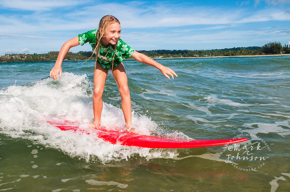 7 year old girl surfing at Hanalei Bay, Kauai, Hawaii people ****Model Release available