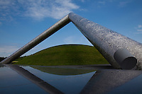 """""""Tetra Mound"""" by Isamu Noguchi installed at Moerenuma Park in Sapporo.  The installation was designed by Noguchi a Japanese-American artist and architect. Construction of the park was begun in 1988, and opened in 2005. The park has won a number of awards including the Good Design Award in 2002.  The park is considered to be one complete sculpture. The triangular sculpture over a grassy mound is called """"Tetra Mound""""."""