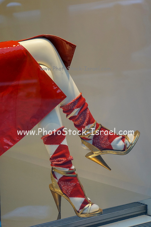 Red raincoat socks and high heel stiletto shoes on a dummy in a shop window