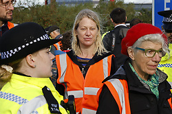 © Licensed to London News Pictures. 27/09/2021. London, UK. Insulate Britain climate activist Cathy Eastburn is detained after blocking a roundabout over the M25 motorway leading to Heathrow airport. Climate activists have vowed to continue their campaign of disruption despite the government being granted a temporary High Court Injucntion banning the group from protesting on the M25. Photo credit: Peter Macdiarmid/LNP