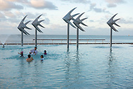 Cairns, Australia - August 15, 2017: Shortly before sunset, tourists enjoy being in the water at the Esplanade Swimming Lagoon, a pool and public park beside the sea. The Fish sculpture is the work of Torres Strait artist Brian Robinson.