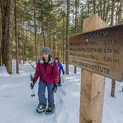 A woman and her showshoeing on the Upper Works Trail, Tahawus Tract, Newcomb, New York. Adirondack Mountains.