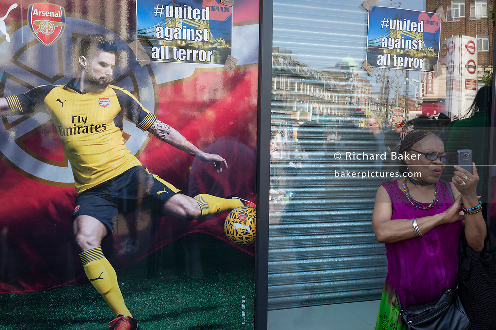 Following the attack on a group of Muslim men outside the Finsbury Park mosque which killed one person and seriously injured another ten, locals stand near defiant messages stuck to the Arsenal football shop window, on 19th June 2017, in the borough of Islington, north London, England
