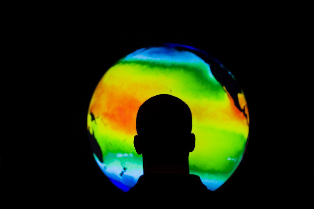 A student observes satellite data of the Earth (mean sea surface temperature) projected onto a sphere at the Fiske Planetarium at the University of Colorado campus in Boulder, Colorado.