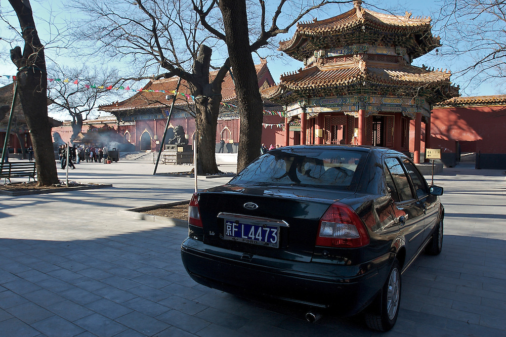 A car is precariously parked to the side of Yonghegong, a Lama Temple in northern Beijing, China.