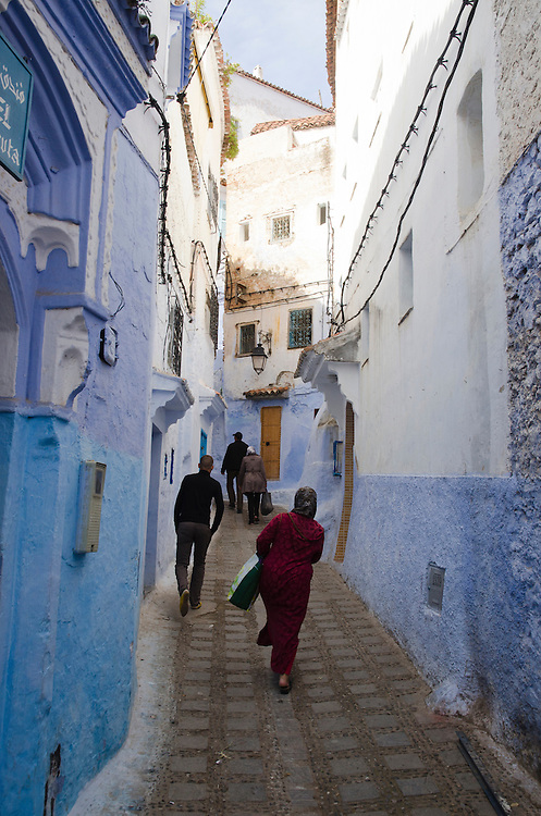 People walk through blue-walled Chefchaouen's medina, Morocco