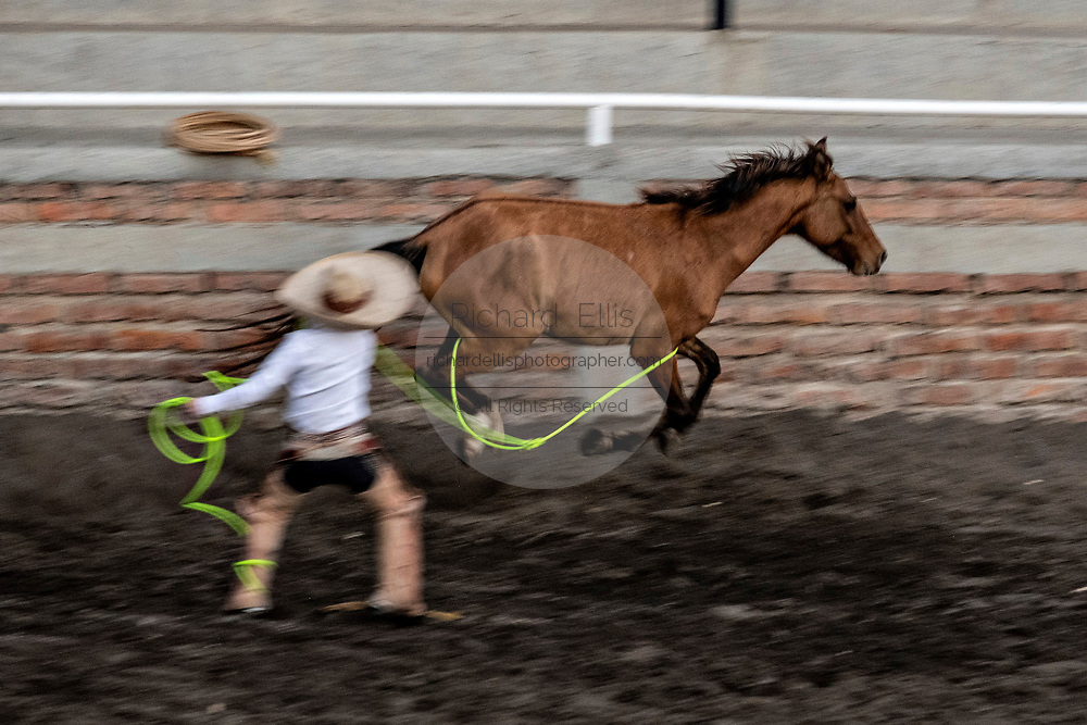 Eight-year-old Juan Franco, from the legendary Franco family of Charro champions, ropes a wild mare during a practice session in the Jalisco Highlands town of Capilla de Guadalupe, Mexico. The roping event is called Manganas a Pie or Roping on Foot and involves a charro on foot roping a wild mare by its front legs to cause it to fall and roll once. The wild mare is chased around the ring by three mounted charros.