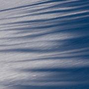 Sunrise shadows across the forzen snow Glacier National Park.