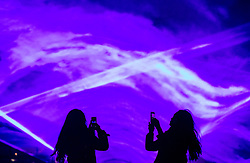 © Licensed to London News Pictures. 17/01/2018. London, UK. Visitors photograph a laser and smoke light show entitled 'Waterlicht' by Daan Roosegaarde as it fills the night sky above Granary Square in King's Cross during the Lumiere London festival. Running from 18th-21st January 2018 more than 50 artworks? are transforming the capital's streets, buildings and public spaces into an immersive nocturnal art exhibition of light and sound. Locations include King's Cross, Fitzrovia, Mayfair, West End, Trafalgar Square, Westminster, Victoria, South Bank and Waterloo. Photo credit: Peter Macdiarmid/LNP