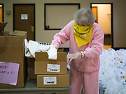 06 APRIL 2020 - DES MOINES, IOWA: MARIA CUNNINGHAM, a volunteer, packs food boxes before a drive through emergency food distribution at First DSM Church in Des Moines. On Monday, 06 April, Iowa reported 946 confirmed cases of the Novel Coronavirus (SARS-CoV-2) and COVID-19. There have been 25 deaths attributed to COVID-19 in Iowa. Most non-essential businesses are closed until 30 April. Well over 100,000 Iowans filed first time claims for unemployment in the last three weeks, more than applied during the peak of the Great Recession of 2008. Local food banks have seen an equal spike in people seeking nutritional assistance. First DSM Church has increased their food pantry from one day weekly to three days per week. Hundreds of people lined up Monday to get a box of food and one roll of toilet paper at the church's drive through pantry.          PHOTO BY JACK KURTZ