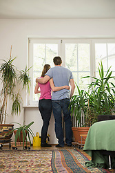 Rear view of a couple standing in living room and looking through window, Munich, Bavaria, Germany