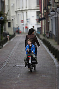 Een jongen zit achterop bij een vrouw op de fiets in de Korte Smeestraat in Utrecht.<br /> <br /> A boy is sitting backwards on a bike at the Korte Smeestraat in Utrecht.