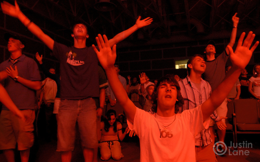 Young men and women are seen praying during a Friday night service featuring religious rock music, sophisticated lighting, and intense prayer for college-age Christians at New Life Church in Colorado Springs, CO on July 8, 2005.