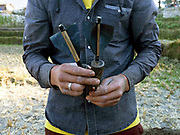 A young Bhutanese man holds darts used for playing 'khuru' a darts game played by men on a field about 20m long with small wooden targets, Sopsokha village, Western Bhutan. The darts are usually homemade from a block of wood and a nail, with chicken feathers or plastic for flights.