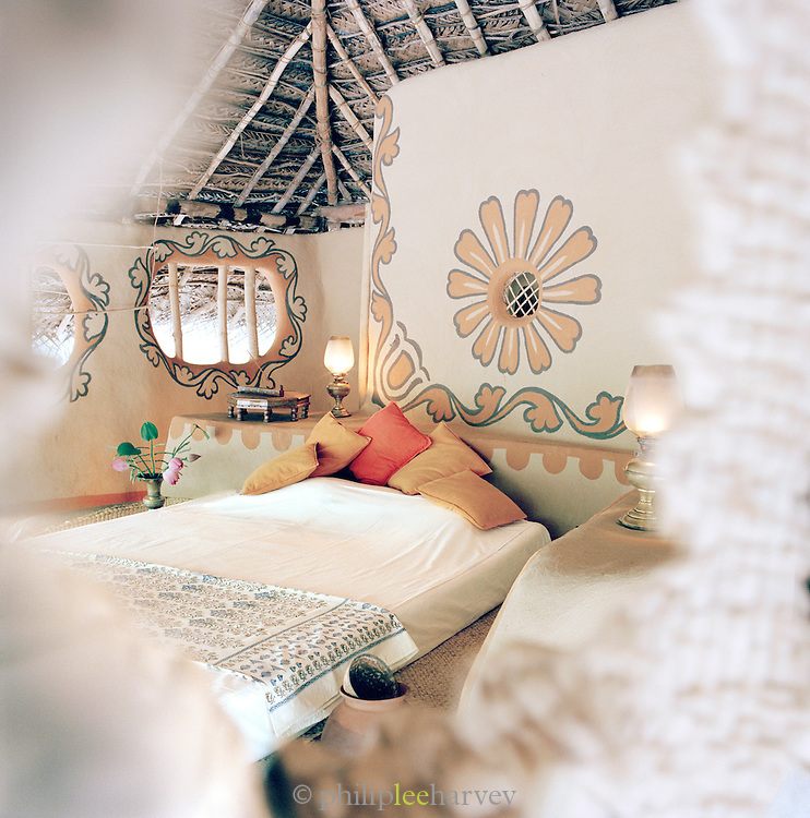 An open-sided mud-hut bedroom in Ulpotha, Sri Lanka, furnished in local fabrics