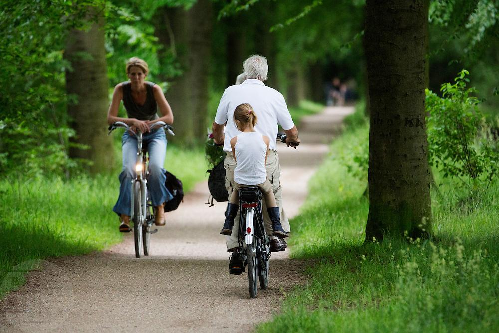 In de omgeving van Soest genieten mensen op de fiets van het mooie weer tijdens het Pinksterweekeinde. Een meisje zit achterop de fiets.<br /> <br /> Near Soest people are enjoying the nice weather by bike.