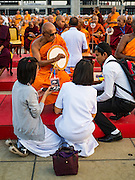 """22 FEBRUARY 2016 - KHLONG LUANG, PATHUM THANI, THAILAND:  A monk talks to devotees during the Makha Bucha Day service at Wat Phra Dhammakaya.  Makha Bucha Day is a public holiday in Cambodia, Laos, Myanmar and Thailand. Many people go to the temple to perform merit-making activities on Makha Bucha Day, which marks four important events in Buddhism: 1,250 disciples came to see the Buddha without being summoned, all of them were Arhantas, Enlightened Ones, and all were ordained by the Buddha himself. The Buddha gave those Arhantas the principles of Buddhism, called """"The ovadhapatimokha"""". Those principles are:  1) To cease from all evil, 2) To do what is good, 3) To cleanse one's mind. The Buddha delivered an important sermon on that day which laid down the principles of the Buddhist teachings. In Thailand, this teaching has been dubbed the """"Heart of Buddhism."""" Wat Phra Dhammakaya is the center of the Dhammakaya Movement, a Buddhist sect founded in the 1970s and led by Phra Dhammachayo.     PHOTO BY JACK KURTZ"""