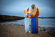 To mark the UN International Migrants Day (18th December 2020) Folkestone community members staged a Nativity scene with Jesus, Mary and Joseph arriving as refugees onto the harbour Bech in Folkestone, Kent, on the 12th of December 2020.  Although they were dressed as Mary and Joseph and appeared to have the baby Jesus with them, they were in fact Rishan and Grmalem, an Ambassador and a Trainee with Kent Refugee Action Network. Both are Christians and refugees from Eritrea. Whilst Jesus was, in fact a doll. (photo by Andy Aitchison)