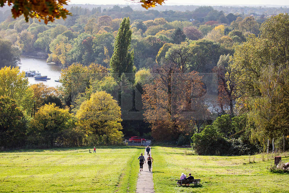 © Licensed to London News Pictures. 21/10/2020. London, UK. Walkers enjoy the autumnal colours over Richmond and Petersham from Richmond Hill in South West London as weather forecaster predict a spectacular display of autumn colours for 2020. However, the Met office have warned of heavy rain and winds for tomorrow but with a sunny and mild outlook for the rest of the week. Photo credit: Alex Lentati/LNP
