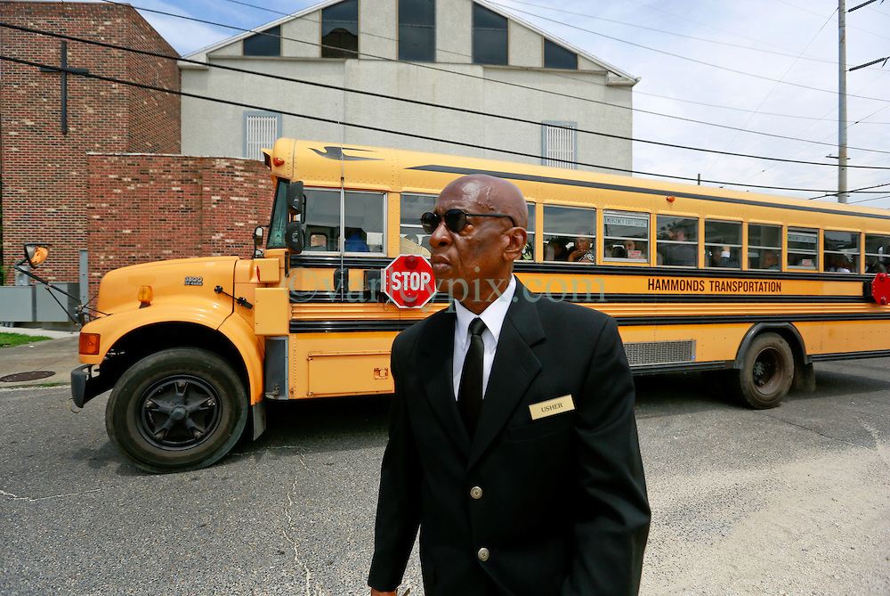 14 May 2014. New Orleans, Lousiana. <br /> A school bus filled with classmates of the victim passes an usher at the funeral for teenage shooting victim Miqual Jackson at the New Hope Baptist Church. 14 years old Jackson was shot in the back of the head May 5th and died shortly afterwards. His 15 year old brother  Lamichael was hit in the leg and survived. 52 year old Gregory Johnson is wanted on 1st degree murder charges. Randy Pittman, 49, an associate of Johnson's was arrested on 3 counts of being a principal to 1st degree murder. The New Hope Baptist Church witnessed the funeral of 1 year old Londyn Samuels who was also gunned down in cold blood on the streets of New Orleans 8 months ago.<br /> Charlie Varley/varleypix.com