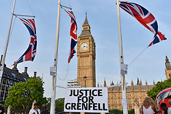 © Licensed to London News Pictures. 19/06/2017. London, UK. Signs affixed to flagpoles as people gather for a vigil in Parliament Square to remember those who died in the Grenfell Tower fire in North Kensington of 14 June.  Mourners and wellwishers were given the opportunity to speak and to write messages on a community banner.  Photo credit : Stephen Chung/LNP