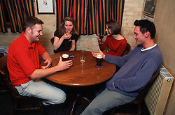 Group of students sitting around table in pub drinking beer and wine,