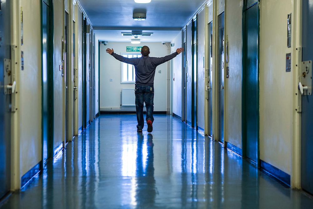 A prisoner walking with his arms out  down one of the corridors of the enhanced wing at <br /> HMP/YOI Portland, Dorset. © Prisonimage.org All image use must be agreed first. All images must be creditied.