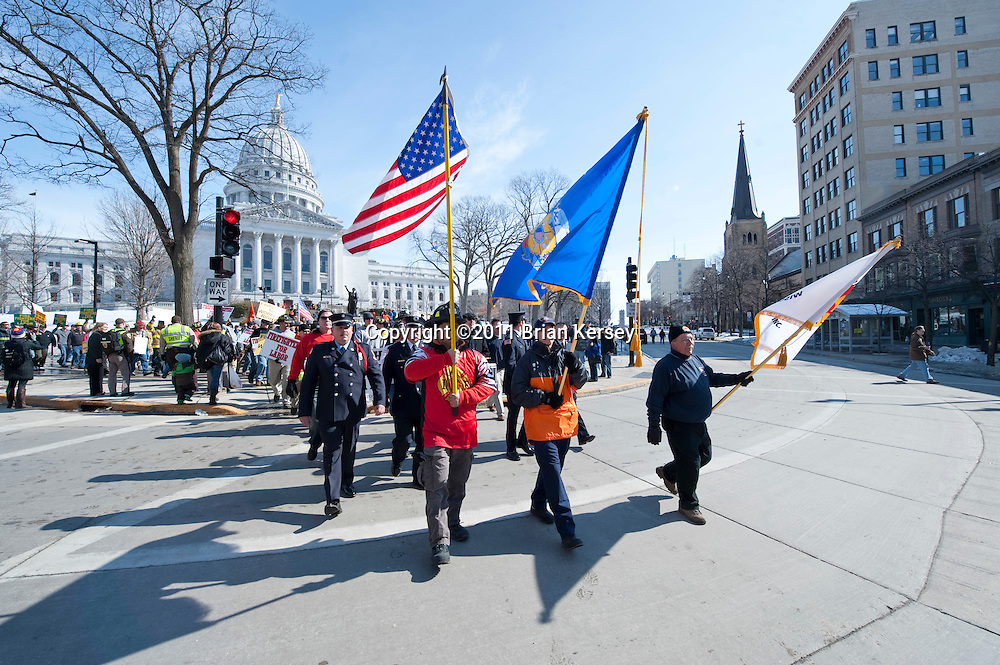 """A group of firefighters marches outside of the state Capitol to protest proposed budget cuts on March 1, 2011 in Madison, Wisconsin. A judge ordered Tuesday that the state Capitol should be opened to the public """"during business hours and at times when governmental matters, such as hearings, listening sessions and court arguments are being conducted."""" Although protesters, occupying the Capitol for 15 days, were not forced to leave, the public was barred from entering the building since it closed at 4 p.m. on Sunday. (Photo by Brian Kersey)"""