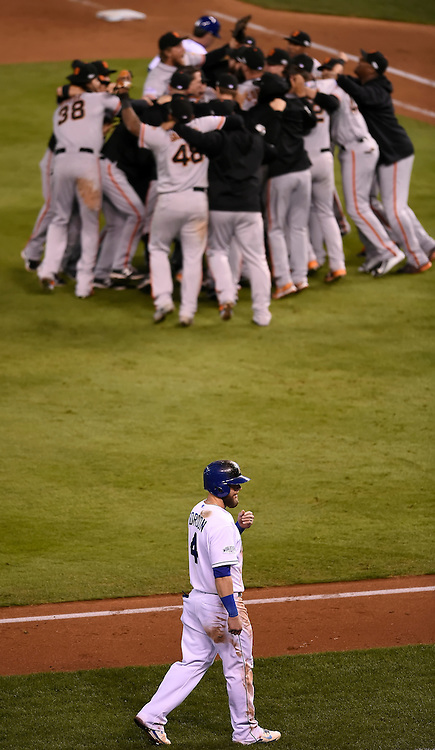 Kansas City Royals left fielder Alex Gordon (4) walked back to the dugout after being stranded on third base in the ninth inning as the San Francisco Giants team celebrated winning Game 7 of the World Series on October 30, 2014 at Kauffman Stadium in Kansas City, Mo. The Giants won, 3-2.
