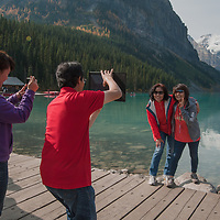 Tourists photograph their companions at Lake Louise in Banff National Park, Alberta, Canada.