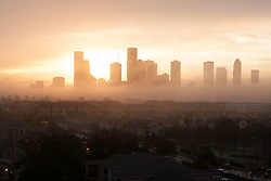 Houston, Texas skyline in foggy sunrise from west with residential neighborhood in foreground.