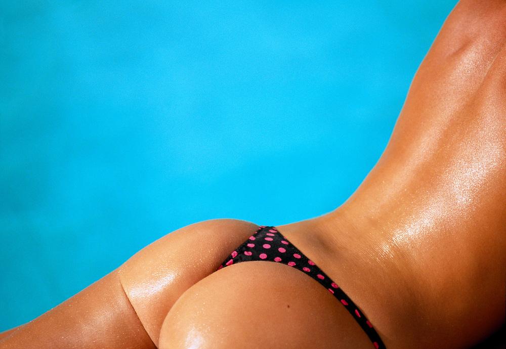 Glistening, tan woman's torso laying next to swimming pool