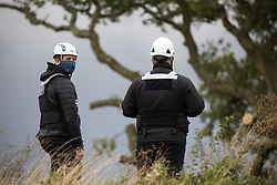 National Eviction Team enforcement agents watch tree surgeons working on behalf of HS2 Ltd fell a 200-year-old oak tree alongside the East West Rail route known locally as the '7 Sisters Oak' as part of works connected to the HS2 high-speed rail link on 23 September 2020 in Steeple Claydon, United Kingdom. A small group of local people and anti-HS2 activists based at the nearby Poors Piece Conservation Project also observed the felling of the tree, which was home to bats and other species, whilst monitored by a joint force of around fifty bailiffs, security guards and police officers from Thames Valley Police.