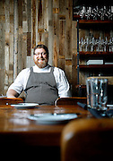 SHOT 8/15/13 4:10:03 PM - Justin Brunson, Owner and Executive Chef at Old Major, poses for a portrait in the main dining room at the restaurant in Denver, Co.  The restaurant focuses on heritage-raised meats from Colorado farms, features an in-house butchery program and bills itself as contemporary farmhouse cuisine. (Photo by Marc Piscotty / © 2013)