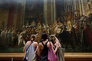 Three young women tourists admire The Coronation of Napoleon (Le Sacre de Napoléon), a painting of almost 10 x 6 metres completed in 1807 by Jacques-Louis David, the official painter of Napoleon. The crowning and the coronation took place at Notre-Dame de Paris, a way for Napoleon to make it clear that he was a son of the Revolution.
