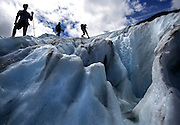 Research assistants navigate around a supraglacial stream on Sholes Glacier as they make measurements to assess the volume lost.<br />